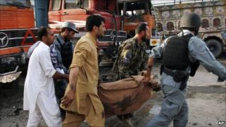 Afghans carry a victim of the bomb attack in Jalalabad