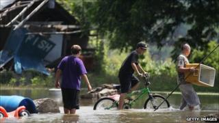 Boys walking through flood waters