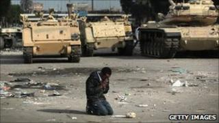 A protester prays near Egyptian army vehicles in Cairo. Photo: February 2011
