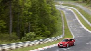 BBC reporter Jorn Madslien driving a salsa red Jaguar KFR at the Nurburgring