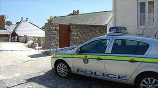 Police car and tape cordoning off the house