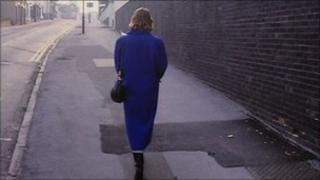 A woman in a blue coat walks down a street alone