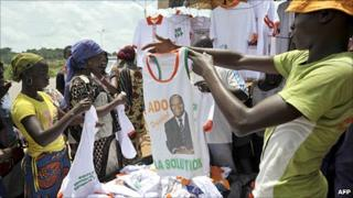 A vendor sells T-shirts bearing the portrait of Ivory Coast President Alassane Ouattara at a market in Yamoussoukro