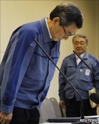 Tepco president Masataka Shimizu (L) bows while the company's managing director Toshio Nishizawa looks on
