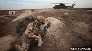 A British soldier watches as a helicopter arrives