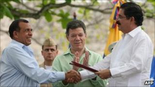 President Lobo (l) and former president Zelaya (r) shake hands as Colombian President Juan Manuel Santos (m) applauds
