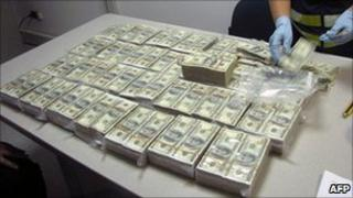 Police officer counts the money found in the hand luggage of a passenger arriving from Mexico