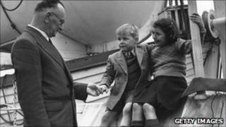 Mr Kitson, agent-general for Western Australia, with two young children about to depart for Australia (18 Dec 1948)