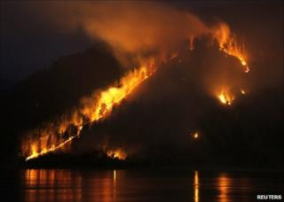 A wildfire burns through woods on a bank of the Yenisei river near Krasnoyarsk, Russia, 21 April