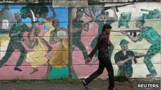 A man walks past a mural depicting fighting during the war in Colombo April 27, 2011