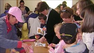 people looking at a craft table
