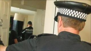 Police officer entering a flat during the drugs raid