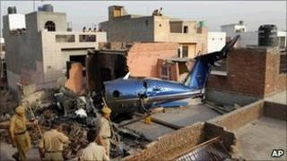 Police officers gather near the site of the plane crash in Faridabad on 26 May 2011