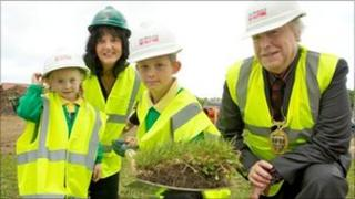 Two pupils help cut the first sod