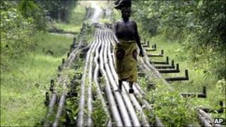 A woman walks along an oil pipeline near in Warri, Nigeria (Archive photograph - 2006)