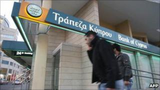 Two men walk past a Bank of Cyprus branch in Nicosia, Cyprus.