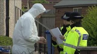 Forensics officer speaks to uniformed officers