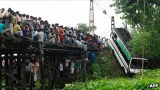 Indian bystanders look on as a crane lifts the wreckage of a bus which crashed in the village of Charabari, Kamrup District, some 60kms from Guwahati on May 31, 2011.