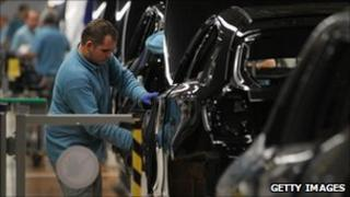 A factory worker works on a car in a BMW plant in Leipzig