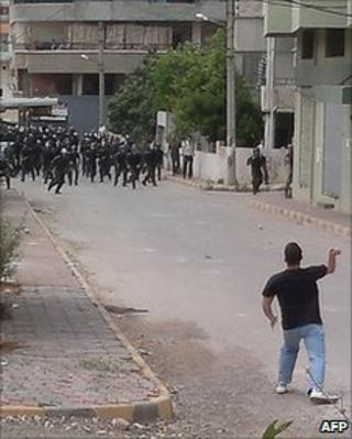 Police run towards a man in Baniyas, Syria, 27 May 2011