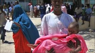 A medical staff member at Medina hospital carries a child injured in a mortar attack in southern Mogadishu on 25 May 2011