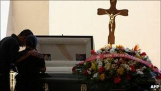 Mourners grieve at the casket of murdered news photographer Luis Carlos Santiago