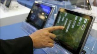 A visitor plays with a tablet PC at the Intel booth during the Computex 2011 computer fair.