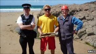 RNLI lifeguard Cameron Coulson, Police Officer Ben De La Haye, and Explosive Technician Stuart Elliott with the detonated device