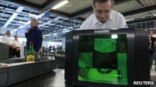 Airport staff in Germany demonstrate a new liquid scanner