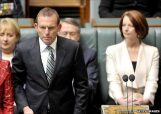 Australian Prime Minister Julia Gillard (right) listens as opposition leader Tony Abbott (left) is sworn in at the House of Representatives, Canberra, 28 September 2010