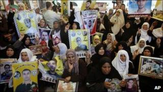 Palestinian women hold pictures of relatives held in Israeli jails during a weekly protest calling for the release of Palestinian prisoners, in Gaza City, 9 May 2011
