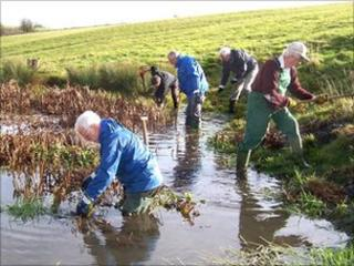 Voluntary wardens at work clearing a pond in the Cotswolds