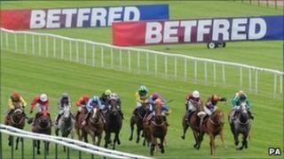 Horses race in front of Betfred signs