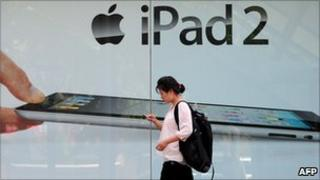 A woman in Bejing checks her cell phone while walking past advertising for the iPad 2.