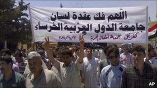 "Mobile phone photo of a protest in the northern Syrian town of Idlib. Banner reads: ""May God help break the silence of the Arab League"" (3 June 2011)"