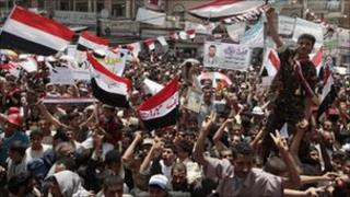 Anti-government protesters spray foam and wave the national flag to celebrate Yemeni President Ali Abdullah Saleh's departure to Saudi Arabia in Sanaa