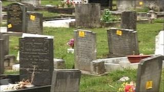 Yellow warning stickers on headstones