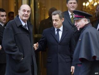 Former French President Jacques Chirac and his successor Nicolas Sarkozy emerge from a Paris restaurant, 21 January 2011