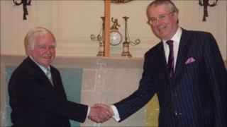 AIHS President General Dr Kevin M Cahill and Ian Whyte shake hands as the flag is officially handed over