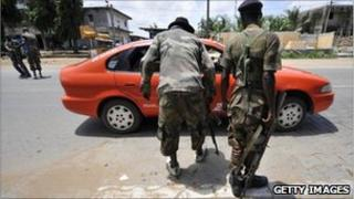 Forces loyal to Ivory Coast's President Alassane Ouattara inspect cars (archive shot)
