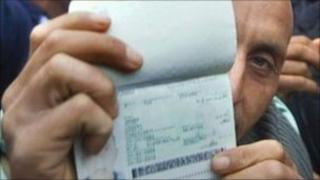 A Tunisian-born immigrant in France shows his passport during a protest, 28 April 2011