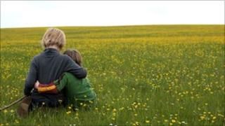 Boys hugging in grassy field