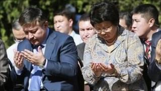 Kyrgyz President Roza Otunbayeva (R) and Parliament Speaker Ahmatbek Keldibekov (L) pray during a ceremony of remembrance in the city of Osh June 10, 2011