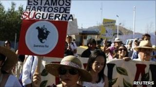 """Protesters in El Paso, Texas hold a banner saying """"We are tired of your war"""" (11 June 2011)"""