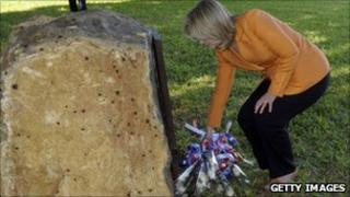 US Secretary of State Hillary Rodham Clinton lays flowers in front of the memorial to the 1998 bombing of the US Embassy in Dar es Salaam, Tanzania