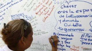 A woman writes a message to Venezuelan President Hugo Chavez on a wall during an event to support him in Caracas June 12, 2011.