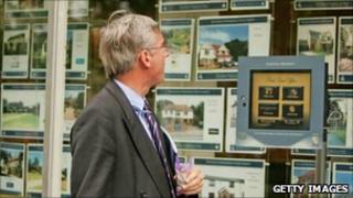 Man looking in estate agents window