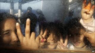 Young girls flash victory signs as they look through their window aboard a ship in Misrata's port