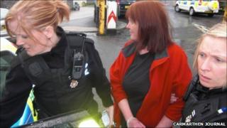 Jacqui Thompson is led away in handcuffs from the council meeting