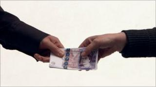 A bundle of £20 notes being passed from one hand to another.